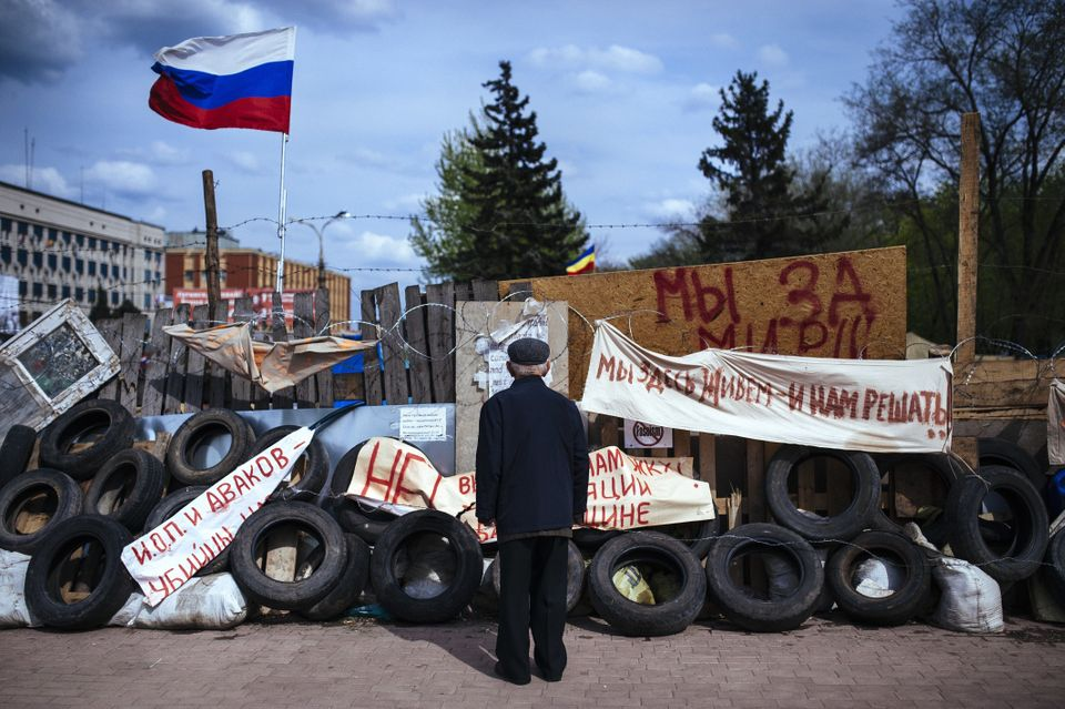 An elderly man stands next a barricade  near the secret service building in the eastern Ukrainian city of Luhansk on April 22