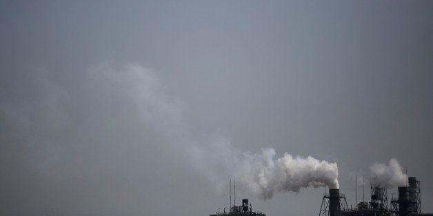 Smoke is discharged from chimneys at a plant in Tokyo, Tuesday, March 25, 2014. Along with the enormous risks global warming
