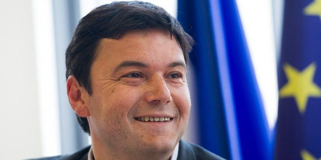 French economist Thomas Piketty smiles during a meeting at the National Assembly on March 13, 2013 in Paris.  AFP PHOTO / FRE