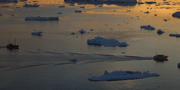 ILULISSAT, GREENLAND - JULY 23:  Ships are seen among the icebergs that broke off from the Jakobshavn Glacier as the sun reac