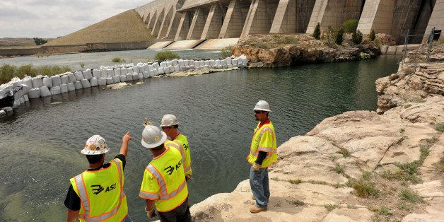 Crews look over the bank of the Arkansas River at the base of the dam of the Pueblo Reservoir, Wednesday, May 18, 2011, are w