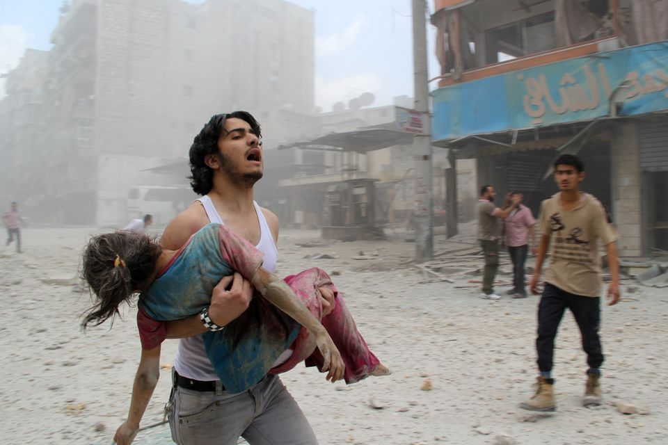 A man carries a young girl who was injured in a reported barrel-bomb attack by government forces on June 3, 2014 in Kallaseh