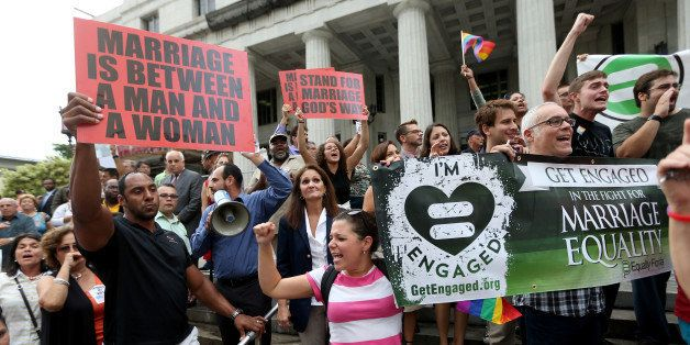 MIAMI, FL - JULY 02:  Opponents of same-sex marriage stand behind a railing near supporters of the LGBTQ couples who are insi