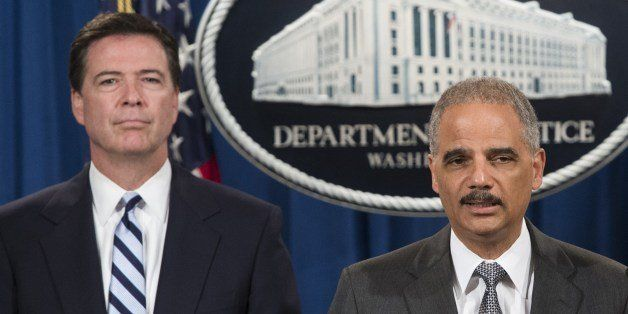 FBI Director James Comey (L) and US Attorney General Eric Holder announce a record 8.9 billion USD fine against the French ba