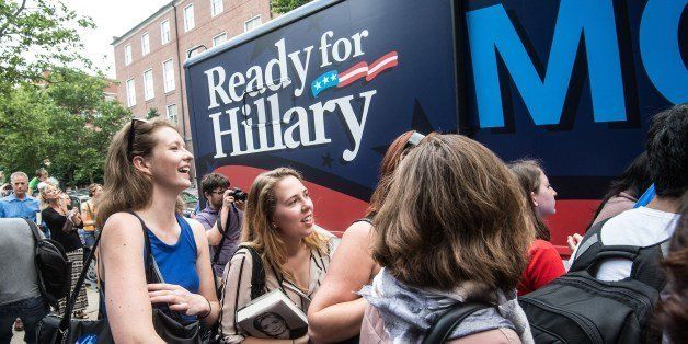 Supporters of former US Secretary of State Hillary Clinton wait as volunteers from Ready for Hillary hand out posters and bum