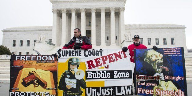 Pro-life demonstrators stand outside the US Supreme Court following oral arguments in the case of McCullen v. Coakley, dealin
