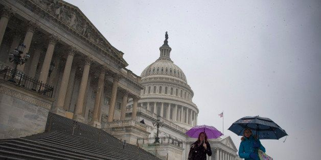 People hold umbrellas as they walk past the US Capitol Building in Washington, DC, December 10, 2013 just as it begins to sno