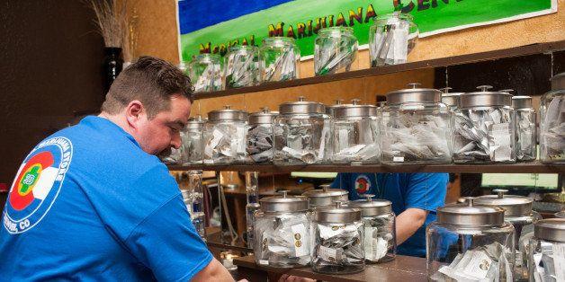 DENVER, CO - JANUARY 1:  Sam Walsh, a budtender, sets up marijuana products as the 3-D Denver Discrete Dispensary prepares to