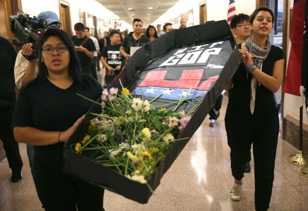 Members of United We Dream, Maria Palacios (L) of Tampa, Florida, and Yadira Dumet (R) of New York City, carry a mock coffin