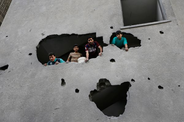 Palestinians from a damaged apartment building inspect the damage to a neighboring building, the offices of the Hamas movemen