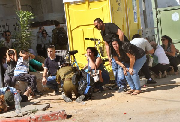 Israeli residents and relatives take cover from a rocket attack from Palestinian militants from the Gaza Strip during the fun