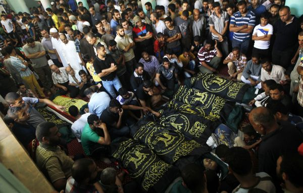 Palestinian mourners gather around the bodies of fifteen members of the Abu zeid, Duheir and al-Hashash families, that were k