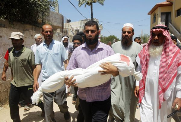 Palestinian relatives carry the body of five year old, Rana Duheir, a Palestinian girl killed in an Israeli air strike, durin
