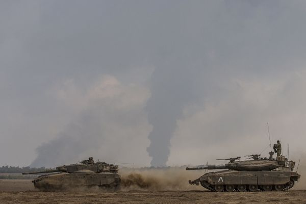 Israeli soldiers and tanks hold their position on the Israeli side of the border with the Hamas-controlled Palestinian territ