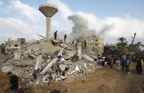 Smoke rises while Palestinian rescuers search for victims under the rubble of the home of the  Duheir family, after it was de