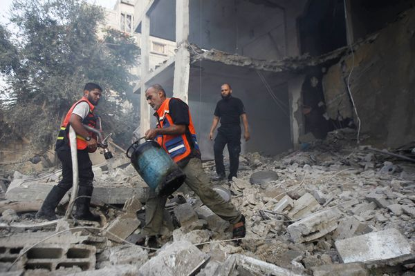 A Palestinian man carries a gas cylinder out of a building as others looks on  after the home was hit by an Israeli air strik