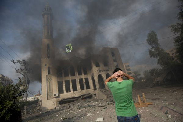 A Palestinian man reacts in front of a destroyed mosque after it was hit by an Israeli air strike, on July 29, 2014, in Gaza