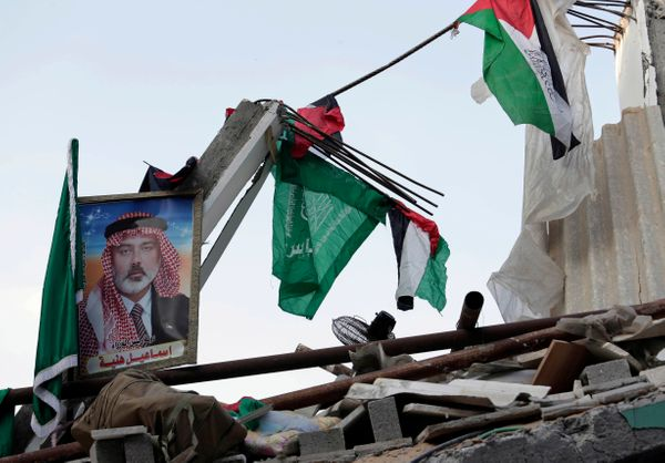 Palestinian and Islamic flags and a portrait of the top Hamas leader in Gaza, Ismail Haniyeh, are placed on the rubble of his