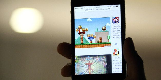 The download page of the 'Super Mario' game on the Beijing Flyfish Technology Co. website is displayed on a smartphone in thi