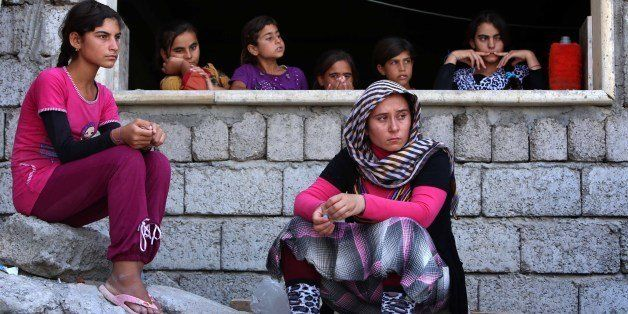 Iraqi Yazidi women who fled the violence in the northern Iraqi town of Sinjar, sit at a school where they are taking shelter
