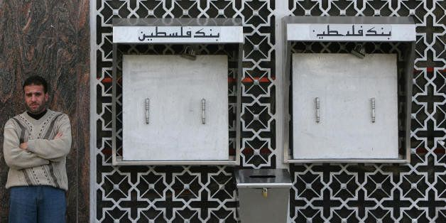 A Palestinian man stands outside a bank with locked ATMs in Gaza city on December 6, 2008. Banks in the Gaza Strip closed the