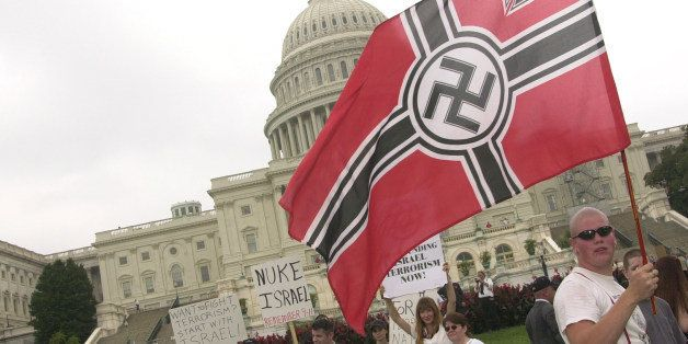 WASHINGTON, :  An unidentified member of the Neo-Nazi National Alliance parades a flag with a swastika in front of the US Cap