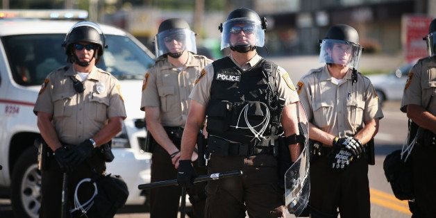 FERGUSON, MO - AUGUST 13: Police watch over demonstrators protest the shooting death of teenager Michael Brown on August 13,