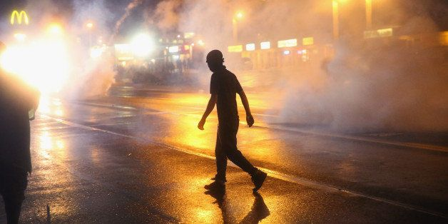 FERGUSON, MO - AUGUST 17:  Police fire tear gas at demonstrators protesting the shooting of Michael Brown after they refused
