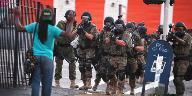 FERGUSON, MO - AUGUST 11:  Police force protestors from the business district into nearby neighborhoods on August 11, 2014 in