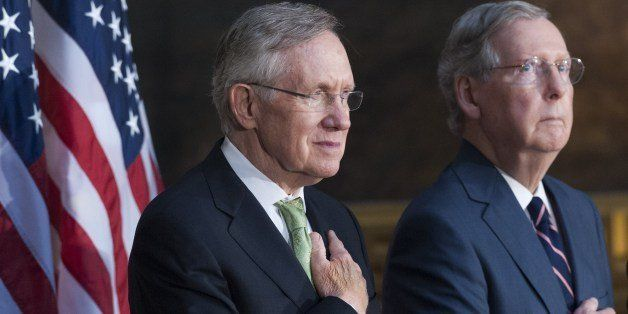 Senate Republican Leader Mitch McConnell (R) and Senate Majority Leader Harry Reid (L) stand during the National Anthem durin