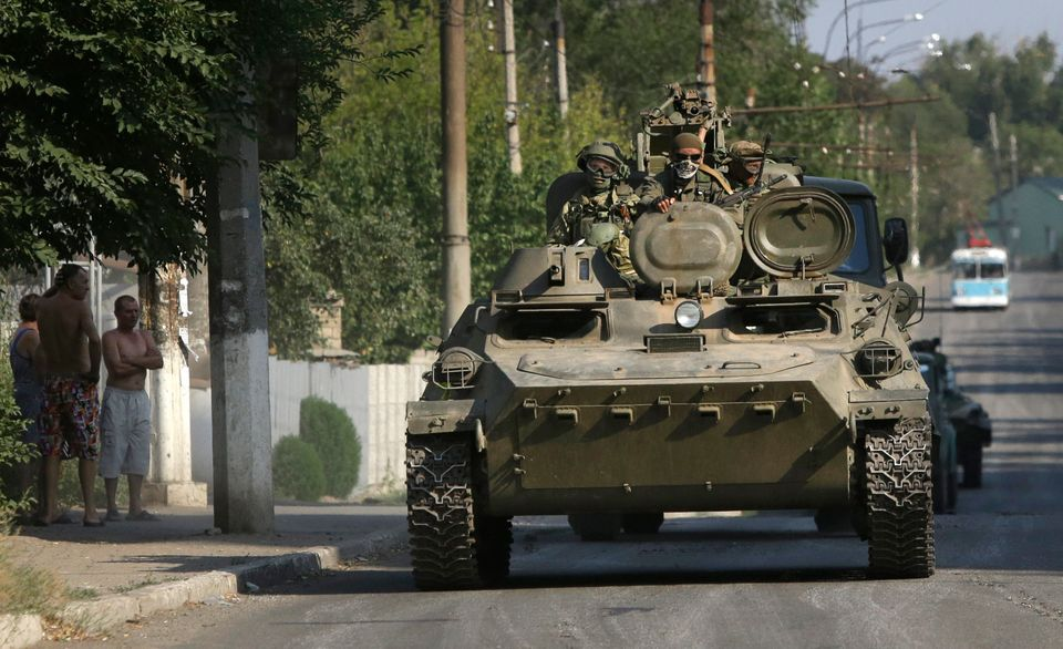 Pro-Russian rebels ride on an APC in the town of Krasnodon, eastern Ukraine, Sunday, Aug. 17, 2014. A column of several dozen