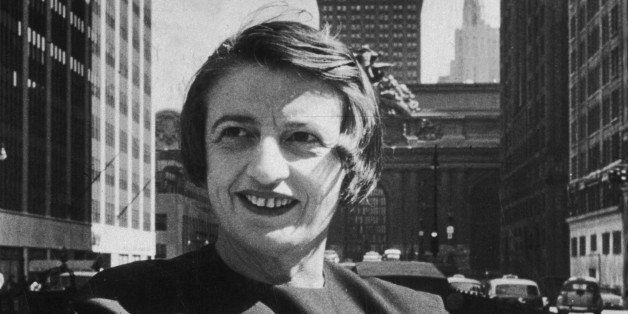 1957:  Russian-born American author and philosopher Ayn Rand, smiles and stands outdoors with her arms folded, in front of th