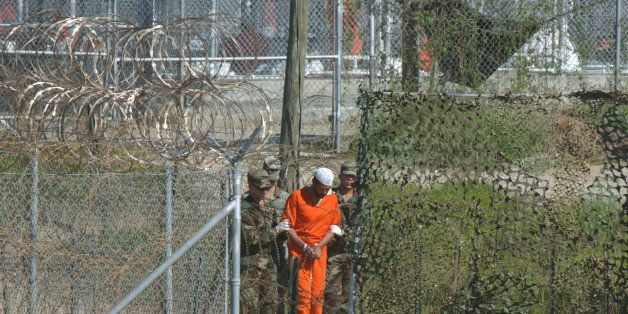 FILE - In this March 1, 2002 file photo, a detainee is escorted to interrogation by U.S. military guards at Camp X-Ray at Gua