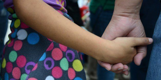 A woman and her daughter hold hands as she speaks to the press upon arriving in San Pedro Sula, about 260 km north of Tegucig