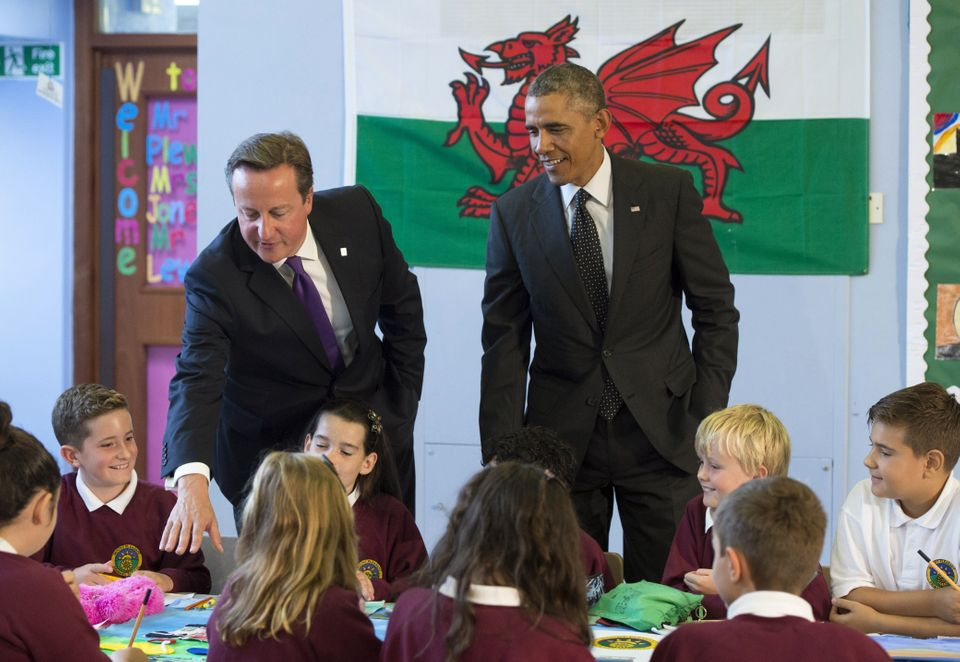 British Prime Minister David Cameron (L) and US President Barack Obama speak with school kids during their visit to Mount Ple