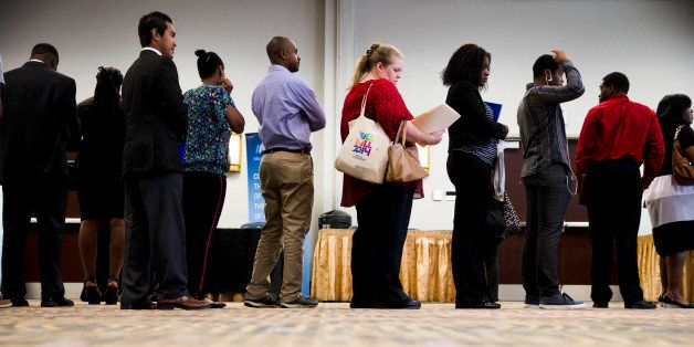 In this June 23, 2014 photo, job seekers wait in line to meet with recruiters during a job fair in Philadelphia. The governme