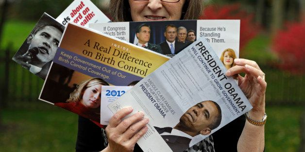 In this photo taken Oct. 19, 2012,  Jean Gianfagna displays some of the political mailers her family receives at her home in