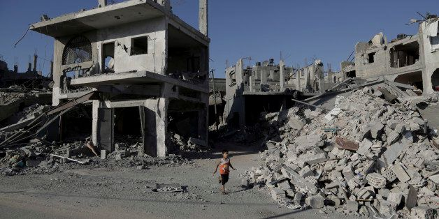 A Palestinian boy runs between the rubble of houses which were hit by an Israeli strikes in Beit Hanoun, in the northern Gaza