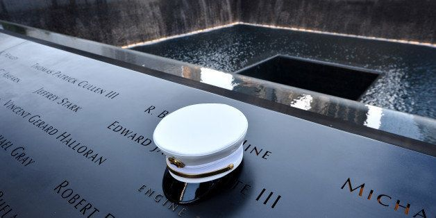 A firefighter's hat sits on names of  firefighters who died at the South Pool, during anniversary ceremonies at the site of t