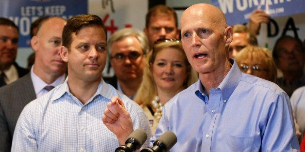 Florida Gov. Rick Scott, right, with running mate for Lt. Gov., Carlos Lopez-Cantera, front left, makes remarks to supporters at a campaign event Monday, Sept. 8, 2014, in Winter Park, Fla. Scott is running against former Republican Gov. Charlie Crist, who is running as a Democrat in November's election for Florida governor. (AP Photo/John Raoux)
