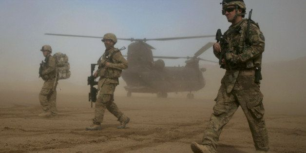 U.S. soldiers part of the NATO- led International Security Assistance Force (ISAF) walks, as a U.S. Chinook helicopter is see