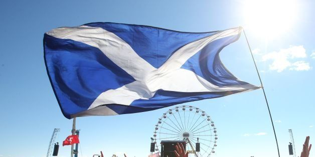 Music fans with a Saltire Flag in front of the Main Stage at the T in the Park music festival held at Balado Park in Kinross,