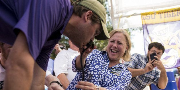 UNITED STATES - SEPTEMBER 20: Sen Mary Landrieu, D-La., holds the beer keg nozzle for LSU football fan as he does a keg stand