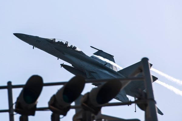 An F/A-18F Super Hornet attached to Strike Fighter Squadron 213 flies over the aircraft carrier USS George H.W. Bush in the P