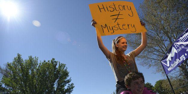 LITTLETON, CO - SEPTEMBER 25:  Otto Schloegl, Senior holds Jennifer Zigler, Senior on his shoulders as she holds up a sign du