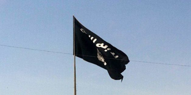 This Tuesday, July 22, 2014 photo shows a motorist passing by a flag of the Islamic State group in central Rawah, 175 miles (