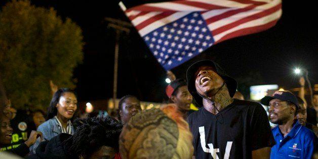 FERGUSON, MO - SEPTEMBER 30:  Protesters gather in front of the police department on September 30, 2014 in Ferguson, Missouri
