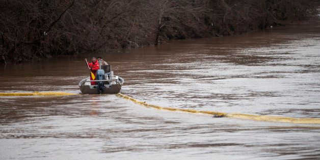 CHARLESTON, WV JANUARY 11, 2014: Emergency crew try to position booms to contain the chemical leak in the Elk River on Satur