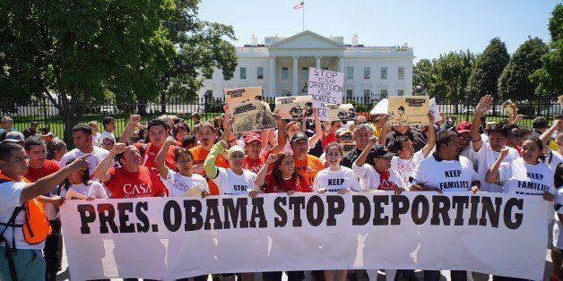 Immigrant rights activists shout slogans in front of the White House on August 28, 2014 in Washington, DC. The demonstrators