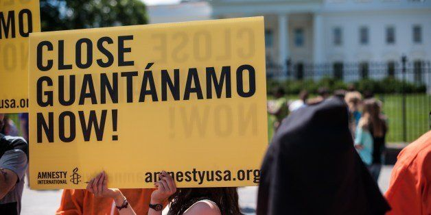 Protestors hold a sign and wear orange prisoners' jumpsuits as they call for the closing of the Guantanamo Bay detention faci